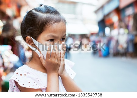 Cute asian child girl wearing protection mask to against air smog pollution with PM 2.5 in the city #1335549758