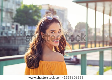 Happy latin woman looking behind while walking on street. Beautiful young woman enjoying vacation during summer. Cheerful girl in smart casual walking and looking at camera while smiling. #1335606335