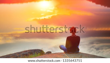 Beautiful woman sits in a pose of a  lotus on high place with amazing view of the lake sunset practice yoga meditation Kundalini energy mindset intuition prana. Solitude harmony mental freedom concept #1335643751