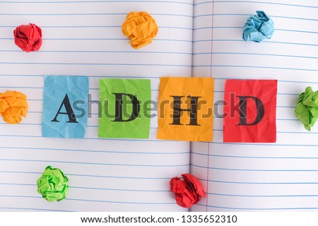 ADHD. Abbreviation ADHD on notebook sheet with some colorful crumpled paper balls around it. Close up. ADHD is Attention deficit hyperactivity disorder. #1335652310