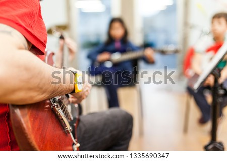 unrecognizable electric guitar teacher teaching young boys at music school #1335690347