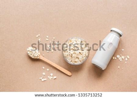Oat milk alternative on beige background, copy space, top view. Healthy vegan substitute dairy free drink - bottle of oat milk. #1335713252