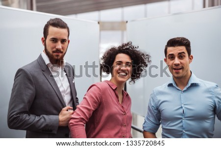 Young businesspeople standing in office, looking at camera. #1335720845