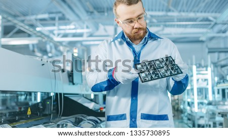 High-Tech Factory: Quality Control Inspector Checks Electronic Printed Circuit Board it for Damages. In the Background Assembly Line for PCB with Surface Mount Pick and Place Technology. Royalty-Free Stock Photo #1335730895