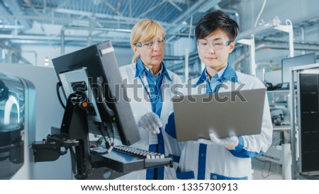 On High Tech Factory Asian Engineer Talks with Female Supervisor, Use Computer for Programming Pick and Place Electronic Machinery for Printed Circuit Board Surface Mount Assembly Line. #1335730913