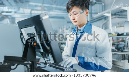 On High Tech Factory Asian Engineer Uses Computer for Programing Pick and Place Electronic Machinery for Printed Circuit Board Surface Mount Assembly Line. Production of PCB with SMT Machinery. #1335730946