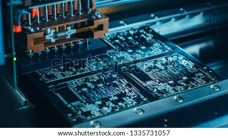 Close-up Macro Shot of Electronic Printed Circuit Board Being Assembled with Automated Robotic Arm, Surface Mounted Technology Connecting Microchips, Transistors, Capacitors to the Motherboard. #1335731057