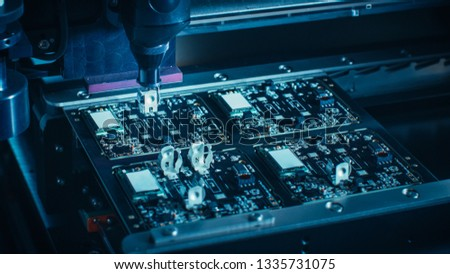 Close-up Macro Shot of Electronic Printed Circuit Board Being Assembled with Automated Robotic Arm, Surface Mounted Technology Connecting Microchips, Transistors, Capacitors to the Motherboard. #1335731075