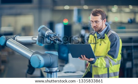 At the Factory: Automation Engineer Uses Laptop for Programming Robotic Arm. New Era in Automatic Manufacturing Industry. #1335833861