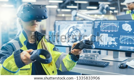 Factory: Female Industrial Engineer Wearing Virtual Reality Headset and Holding Controllers, She Uses VR technology for Industrial Design, Development and Prototyping in CAD Software. #1335833906
