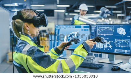 Factory: Female Industrial Engineer Wearing Virtual Reality Headset and Holding Controllers, She Uses VR technology for Industrial Design, Development and Prototyping in CAD Software. #1335833918