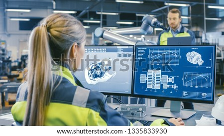 At the Factory: Female Mechanical Engineer Designs 3D Engine on Her Personal Computer. In the Background Male Automation Engineer who Uses Laptop for Programming Robotic Arm. #1335833930