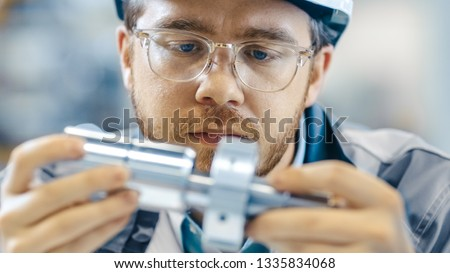 Close-up Shot of the Industrial Engineer Wearing Classes and Hard Hat Connects Two Components He Designed. Precision in Mechanical Engineering. #1335834068