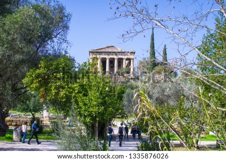 Athens, Greece/ March, 2019: Tourists visiting the archaeological area of the temple of Hephaestus or Hephaisteion, a well preserved greek temple in the western of the ancient Agora in Athens Greece #1335876026