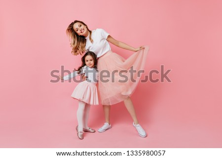 Portrait of beautiful young mother and her little daughter in identical romantic outfit smiling on pink background #1335980057