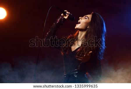 Beautiful singing girl curly afro hair. Beauty woman singer sing with microphone karaoke song on stage. Dark background, smoke, spotlights #1335999635