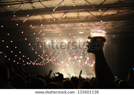 Shot of some fans during a life concert of a famous british band. Focus on a happy man with a beer on his hand. Royalty-Free Stock Photo #133601138
