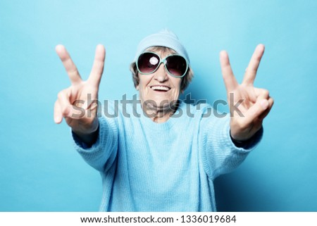 Lifestyle, emotion  and people concept: Funny old lady wearing blue sweater, hat and sunglasses showing victory sign. Isolated on blue background. #1336019684