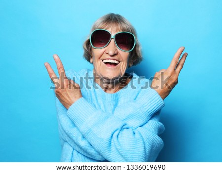 Lifestyle, emotion  and people concept: Funny old lady wearing blue sweater, hat and sunglasses showing victory sign. Isolated on blue background. #1336019690