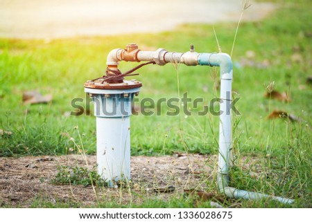 Groundwater well with pvc pipe and system electric deep well submersible pump water on green meadow / groundwater testing and sampling pollution concept #1336028675