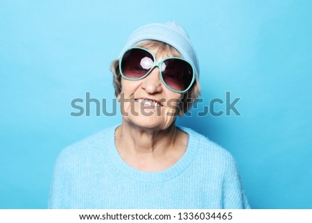 funny happy grandmother wearing blue sweater and sunglasses #1336034465