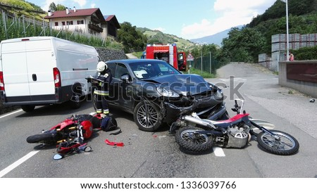 Frontal car accident with two motorbikes and car. Massive motorcycles crash collision hit by car following a risky road overtaking. Firefighter performs accident reconstruction of an multiple crash. Royalty-Free Stock Photo #1336039766