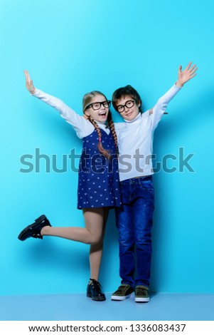 Happy spectacled children are posing on blue  background. Happy childhood. Spring holidays. #1336083437