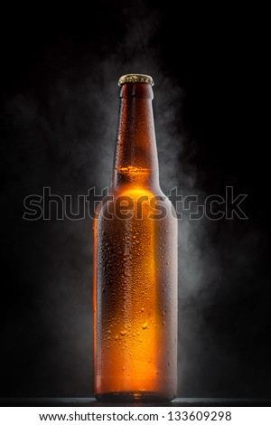 Cold beer bottle with drops, frost and vapour on black Royalty-Free Stock Photo #133609298