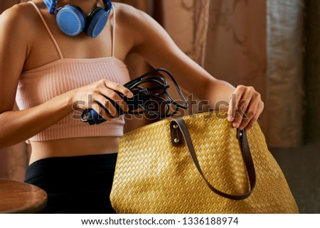 Young woman putting professional jumping rope in bag when getting ready for gym #1336188974
