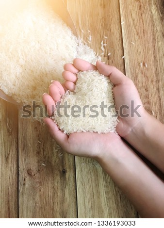 Soft focus- woman hands holding rice on her palms (heart shape) with wooden background #1336193033