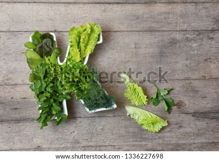 Vitamin K in food concept. Plate in the shape of the letter K with different fresh leafy green vegetables,  lettuce, herbs on wooden background. Flat lay or top view. #1336227698