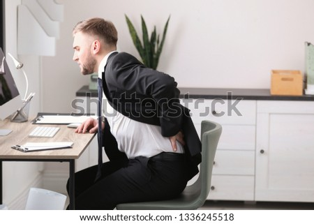 Businessman suffering from back pain at workplace #1336245518