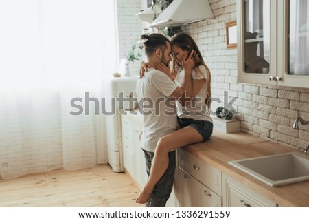 Beautiful loving couple kissing in kitchen #1336291559