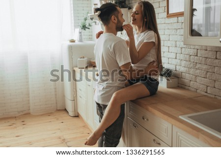 Beautiful loving couple kissing in kitchen #1336291565