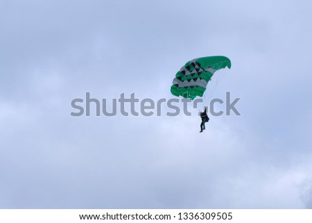 Skydiver is piloting a green parachute. #1336309505