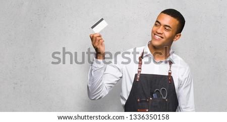 Young afro american barber man holding a credit card and thinking on textured wall