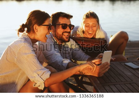 Two young woman and man using smartphone by the river and smiling #1336365188