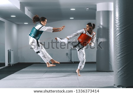 Two Caucasian young women sparring in taekwondo fittings in gym barefoot. #1336373414