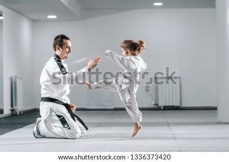Smiling Caucasian taekwondo trainer in dobok kneeling and holding hand up while little girl kicking him. #1336373420