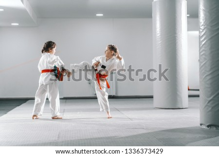 Two young Caucasian girls in doboks having taekwondo training at gym. One girl kicking while other one holding kick target. #1336373429
