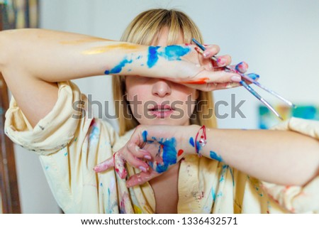 Young blonde beautiful painter covering her face with messy hands #1336432571