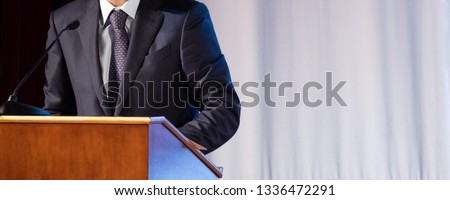 Speech of an abstract man in a suit on stage at the stand for performances. Tribune or pulpit for speaker official, president or professor. Close-up. Copy space. Royalty-Free Stock Photo #1336472291