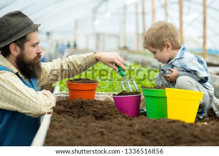 planting together. father and son planting together in greenhouse. happy family planting together. planting flowers together in graden orangery. taking good care of plants #1336516856