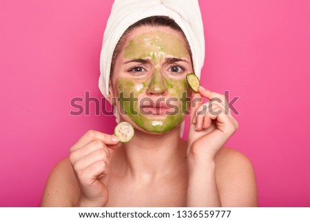 Dissatisfied young cute woman doesnt like smell from beauty mask, discontent with effect, holds two slices of cucmber, removes wrinkles on face, wears white towel, isolated on pink studio wall #1336559777