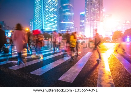 Abstract background of People across the crosswalk at night in Shanghai, China. Perfect background image of blurred night street with unrecognizable people and cars in night illumination  #1336594391
