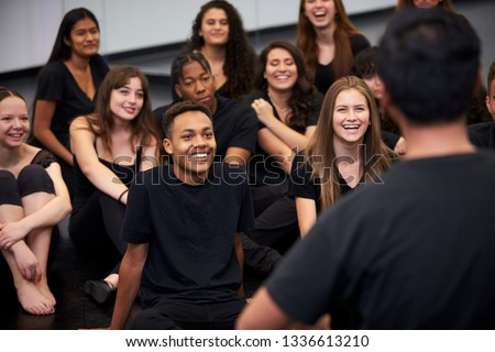 Teacher At Performing Arts School Talking To Students Sitting On Floor In Rehearsal Studio Royalty-Free Stock Photo #1336613210