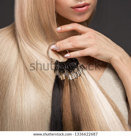 Beautiful blond girl with a perfectly smooth hair, classic make-up with a palette for hair extensions in the hands. Beauty face. Picture taken in the studio. #1336622687