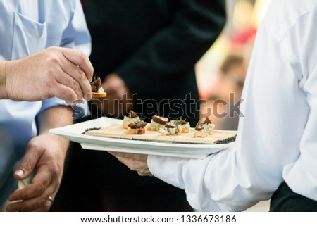 a server holding a tray full of snacks during a catered event #1336673186