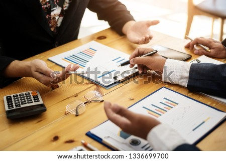 Group of business people discussing with analyzing data financial report at the office desk on montly meeting. Accounting concept. #1336699700