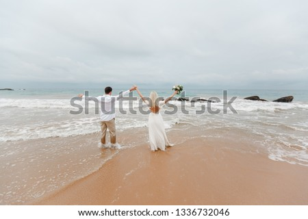 Happy just married couple standing on the beach and holding hands up. Bride and groom back view standing on the beach and looking at the sea #1336732046